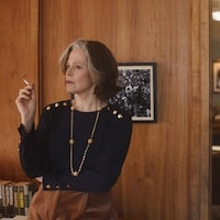 Une femme fume une cigarette, assise sur un meuble dans un bureau. En arrière-plan, on aperçoit une autre femme qui parle au téléphone, assise derrière un bureau.