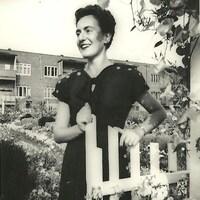 Une femme souriante se tient près d'une clôture