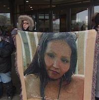 Des proches de Nadine Machiskinic tiennent un portrait de la femme dans leurs mains.