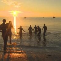 Sept personnes en combinaison de plongée rentrent dans l'eau au lever du soleil.