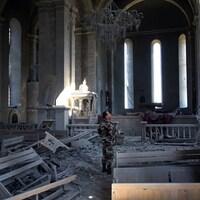 Un soldat se tient dans les ruines d'une église.
