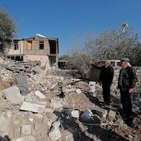 Deux hommes regardent une maison détruite par un bombardement.