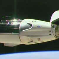 Une capsule spatiale est visible à l'extérieur de la Station spatiale internationale avec une partie de la Terre en dessous.