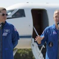 Les astronautes Robert Behnken et Douglas Hurley devant un avion sur une piste de la NASA.