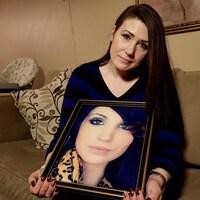 Une jeune femme tient le portrait d'une autre jeune femme.