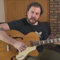 Un homme joue de la guitare chez lui.