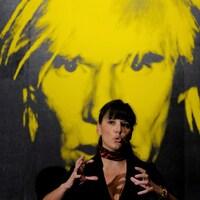 Nathalie Bondil parle devant une peinture d'Andy Warhol.