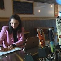 Assise au bar de son restaurant, Nathalie Francoeur consigne ses réservations dans un cahier.