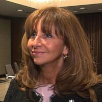 Une femme sourit dans une salle de conférence