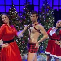 Une femme tient par son doigt un homme, et en arrière e lui, une autre femme est habillée en mère Noël.