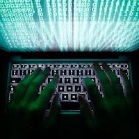Des doigts tapent sur un clavier d'ordinateur devant un écran avec du code informatique.