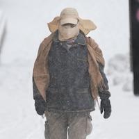 Une personne chaudement vêtue marche sur un trottoir alors que la neige tombe.
