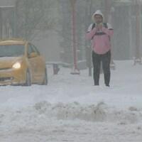Un homme avec seulement une petite veste marche dans la neige. À ses côtés, un taxi jaune est stationné.
