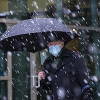Un homme marche sous un parapluie alors qu'il neige à Surrey, dans le Grand Vancouver.