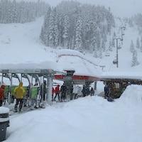 Une dizaine de skieurs en habits d'hiver colorés attendent ou prennent place dans un remonte-pente qui les amènera au sommet d'une montagne enneigée.