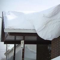 Un gros amas de neige sur un pignon de l'aréna Guy-Carbonneau, à Sept-Îles.