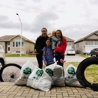 Une mère et ses 3 enfants montrent les sacs remplis d'ordures qu'elles ont ramassées.