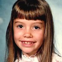 Photo d'une fillette aux cheveux longs portant un chemisier blanc avec une boucle rouge.