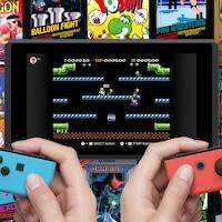 Une image promotionnelle montrant les mains de deux personnes tenant des manettes de Switch pendant qu'un écran affiche une partie de Mario Bros.