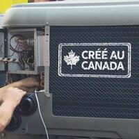 Un homme qui travaille sur une thermopompe sur laquelle ont peut lire : Créé au Canada.