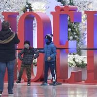 """Une famille pose devant une enseigne """"Noël"""" à Montréal."""