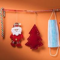 Des décorations de Noël et un masque suspendus à une corde.