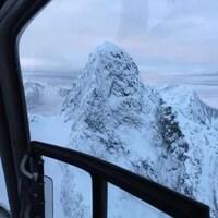 Une montagne enneigée vue du cockpit d'un hélicoptère.