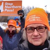 Deux militantes opposées au projet Northern Pass. L'une porte une tuque sur laquelle on peut lire « Stop Northern Pass », l'autre bandit une pancarte arborant le même message.