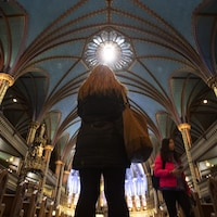 Une touriste dans l'allée centrale de la basilique Notre-Dame à Montréal.
