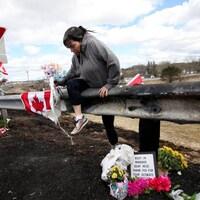 Krista Hughes ramasse des fleurs qui avaient été arrachées d'un mémorial improvisé en l'honneur de la policière Heidi Stevenson, une des 22 victimes de la tuerie.