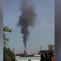 Un nuage de fumée s'échappe d'une cheminée au loin