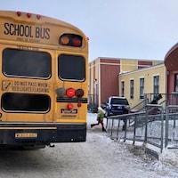 Un autobus scolaire dépose des enfants à l'école.