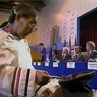 Cérémonie du feu d'une femme inuit. En arrière-plan, le premier ministre Brian Mulroney et les représentants autochtones sont assis au long d'une table pour signer l'accord.