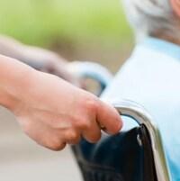 Une femme pousse la chaise roulante d'une personne âgée