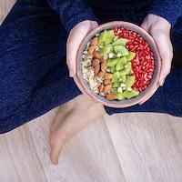 Un bol rempli d'aliments entre les mains d'une femme assise en tailleur sur le sol.