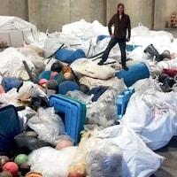 Un bénévole se tient sur un tas de déchets marins.