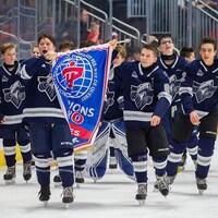 Entouré de ses camarades, un jeune garçon crie de joie en soulevant une bannière sur laquelle on peut lire « Champions ».