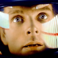 Le visage d'un homme blanc aux yeux bleus, en gros plan, regarde l'horizon. Il porte un scaphandre.