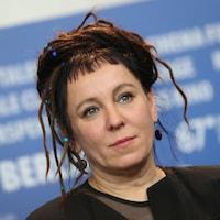 Portrait de Olga Tokarczuk, dont les cheveux sont ornés de perles bleues.