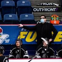Un entraîneur de hockey regarde l'écran géant pendant un match.