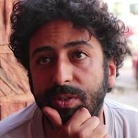 Portrait d'Omar Radi, dans la trentaine, cheveux noirs et bouclés.