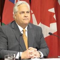 Un homme en veston devant un micro en conférence de presse. Derrière lui, des drapeaux ontariens et canadiens.
