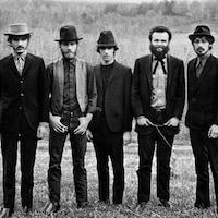 Cinq hommes sont alignés dans un champ.