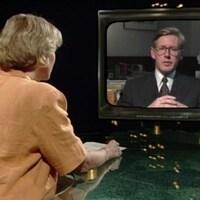 L'animatrice Madeleine Poulin, de dos, discute avec Bob Rae dont l'image est diffusée dans un écran.