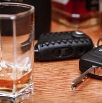 Un verre d'alcool à côté de clés de voiture