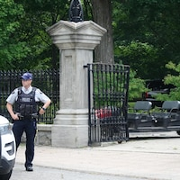 L'agent est devant une grille qui semble avoir été percutée par un petit véhicule.