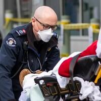 Un ambulancier pousse un brancard.