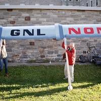 Des opposants au projet de GNL Québec tiennent une grande pancarte.