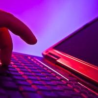 Un homme appuie sur les touches du clavier d'un ordinateur portable
