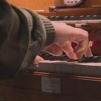Un homme tape sur le clavier de l'orgue située dans l'église Highwood.